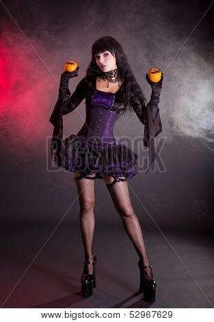 Beautiful witch in purple and black gothic fantasy Halloween costume with Jack lantern oranges