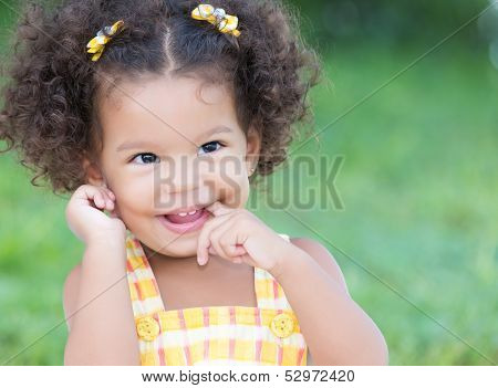 Cute hispanic girl with an afro hairstyle laughing with diffused green grass background