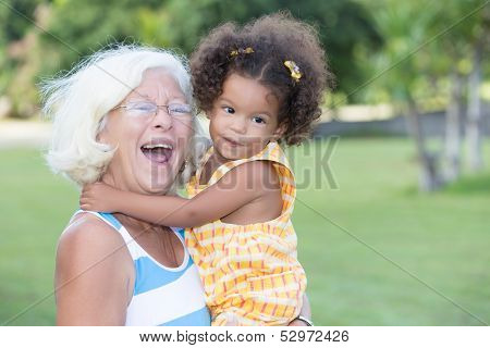 Portrait of a caucasian grandma carrying her little hispanic granddaughter and laughing