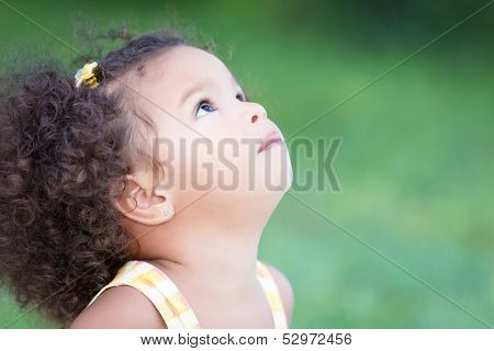 Small hispanic girl with an afro hairstyle looking up with space for text