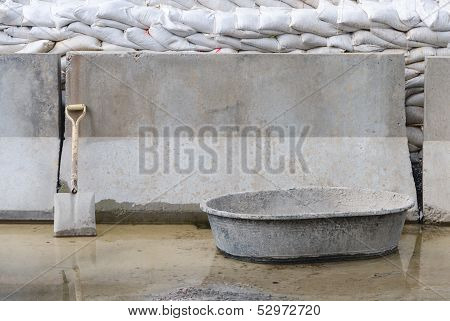 Shovel Leaning Against Wall With Concrete Mixing Container At Construction Site
