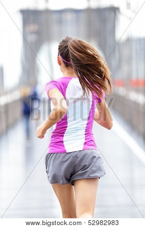 City runner - woman running on Brooklyn Bridge. Rear view backside close up of female athlete training outside in rain in New York City, United States.