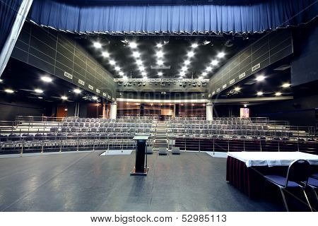 Stage with desk and rows of chairs  in modern black hall for business meetings.