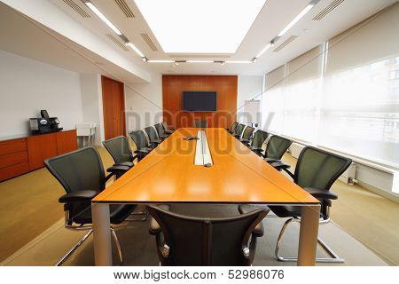 Long wooden table, modern armchairs and tv in light room for business meetings.