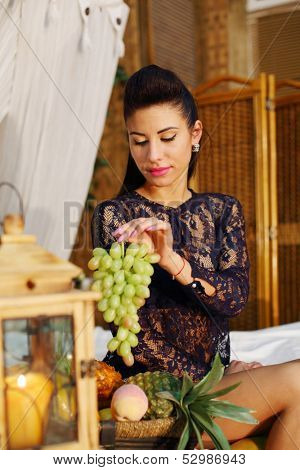 Pretty woman sits on bed and holds bunch of green grapes in bedroom.