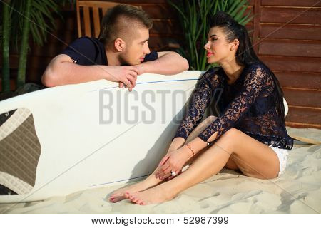 Man with surfboard and young woman sit on sand and look at each other next to beach house.
