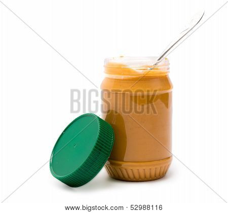 Peanut Butter in a Jar Ready to Serve with Spoon Isolated on a White Background