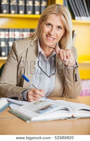 Portrait of happy female teacher with glasses and books sitting at table in university library
