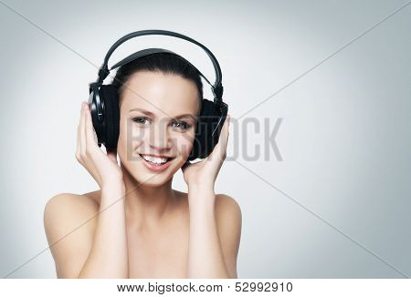 A young and pretty teenage girl listening to the music in headphones