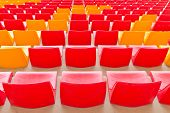 stock photo of grandstand  - Red and Orange Empty Seats in a Grandstand - JPG