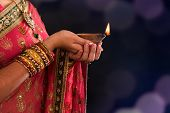picture of sari  - Diwali or deepavali photo with female hands holding oil lamp during festival of light - JPG