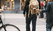 stock photo of carry-on luggage  - Thief stealing wallet from backpack of a man walking on street during daytime - JPG