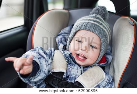Happy Toddler  Boy Sitting In The Car Seat