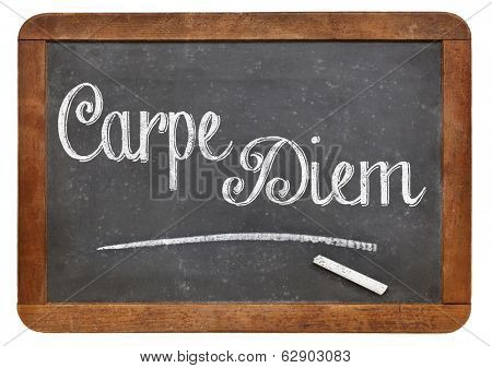 Carpe Diem (make the most of the present time) handwritten with white chalk on a blackboard, isolated on white.