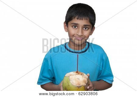 Handsome Indian kid cooling off with fresh coconut