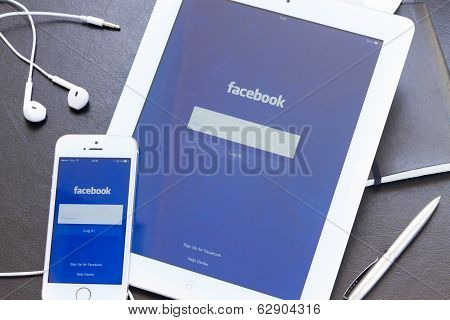 Facebook app on screen of Ipad and Iphone 5s.