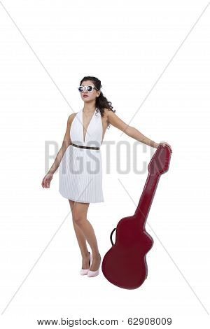 Attractive female wearing sunglasses posing with guitar