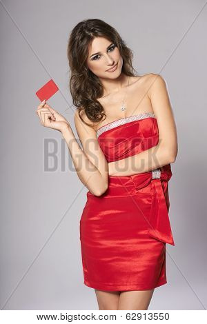 Fashion female in red dress showing red card