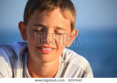 Smiling Teenager Boy Against Sea, Closed Eyes