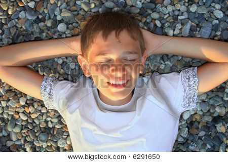 Teenager Boy Lying On Stones On Stone Seacoast, Closed Eyes, Holding Hands Behind Head