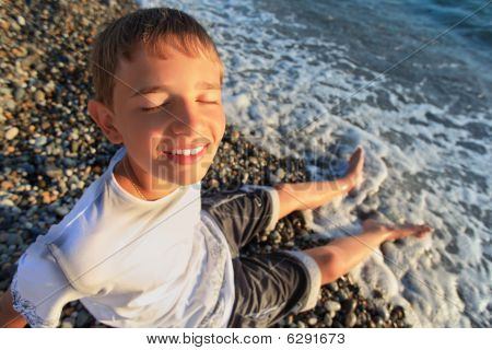 Sitting Teenager Boy On Stone Seacoast, Closed Eyes, Wets Feet In Water