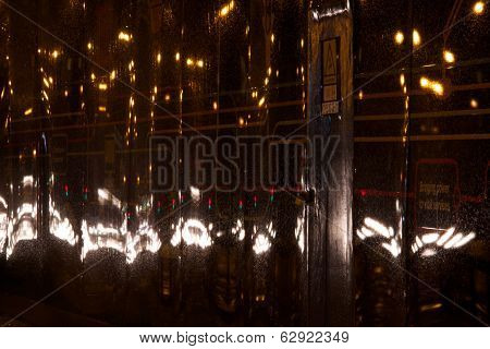 Headlights at night reflected in advertising hoarding