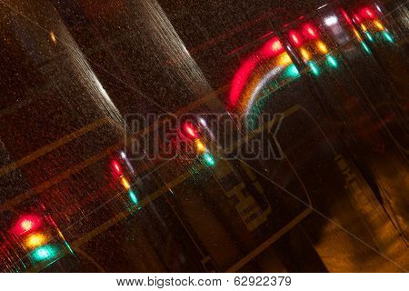 Traffic lights at night reflected in hoarding