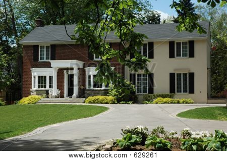 Picture or photo of formal red brick house with stucco for Brick houses without shutters