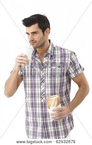 Young man having sandwich and drinking coffee while walking.