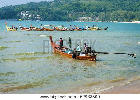 Phuket, Thailand - 19 Mar 2013: Man Cast Off On Wooden Long Boat In Phuket, Thailand. Trip On A Long