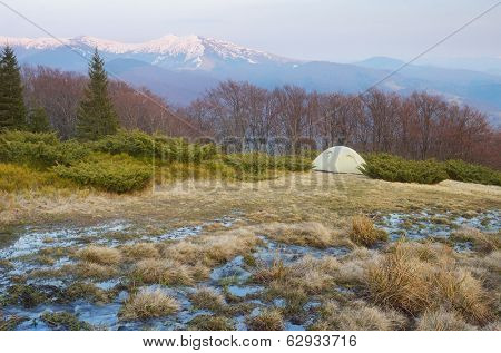 Spring landscape with tourist tent in the mountains. Mountain stream of melted snow. Carpathians, Ukraine, Europe