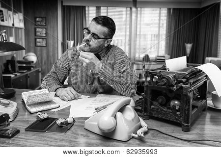 Man Smoking A Cigarette While Work In The Office, 1960's Scene