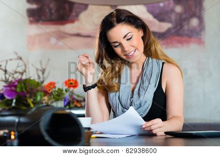 Young woman working or learning in a cafe or restaurant on a contract or some documents