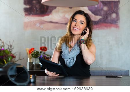 Young woman on the phone in a cafe or restaurant, she using her mobile phone and a tablet computer