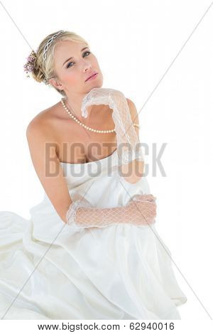 Portrait of sensuous bride with hand on chin against white background