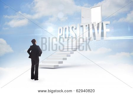 The word positive and businesswoman with hands on hips against steps leading to open door in the sky