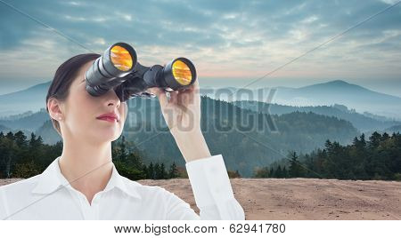 Business woman looking through binoculars against scenic countryside with mountains