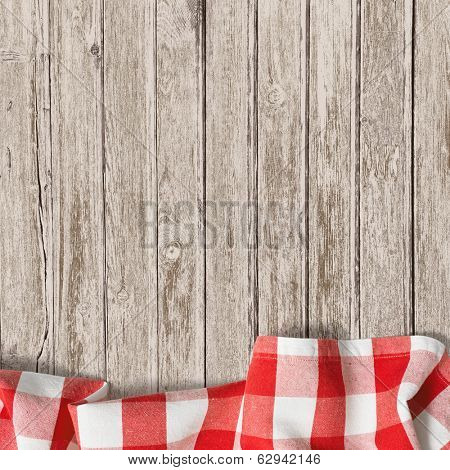 old wooden table with red picnic tablecloth background