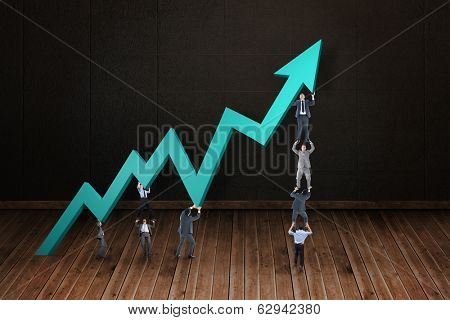 Business teamwork pushing arrow against dark room with floorboards