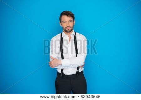 handsome man on blue wearing white shirt and braces on blue