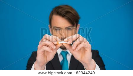 business holding a broken cigarette giving up smoking on blue