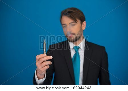 handsome businessman with e-cigarette wearing suit and tie on blue background