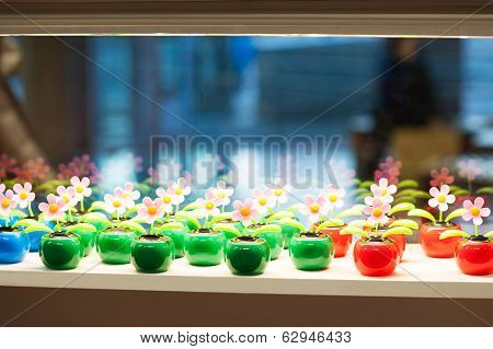 Many Plastic Multicolored Toy Flowers On Glass Shop Window.