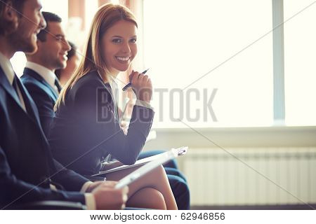 Row of business people sitting at seminar, focus on attentive young female