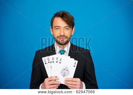 young business man showing playing cards - poker face on blue