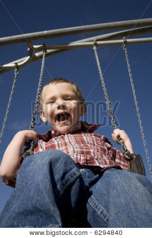 Boy On Swigng Blue Sky