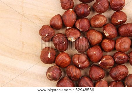 Close up of hazel nuts on a wooden board.