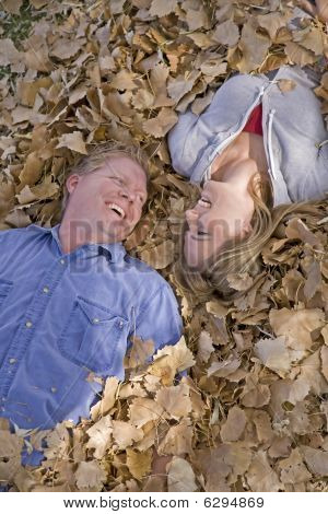 Man And Woman In Leaves Looking At Eachother