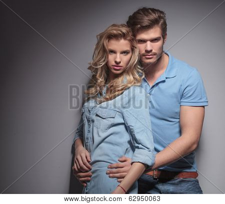 casual man holding his girlfriend close to him , studio picture
