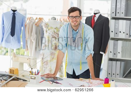 Portrait of a smiling handsome male fashion designer standing in the studio